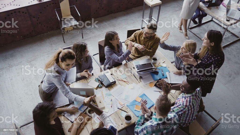 Vista superior del equipo creativo trabaja en la oficina moderna. Colegas, hablando, sonriendo, cinco alto entre sí - foto de stock