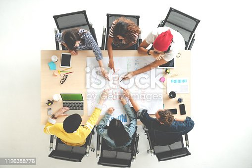 istock Top view of creative diverse people agree result together. Overhead view of young creative team, start up colleagues group or college student meeting and voting agree opinion by pointing hand at desk. 1126388776