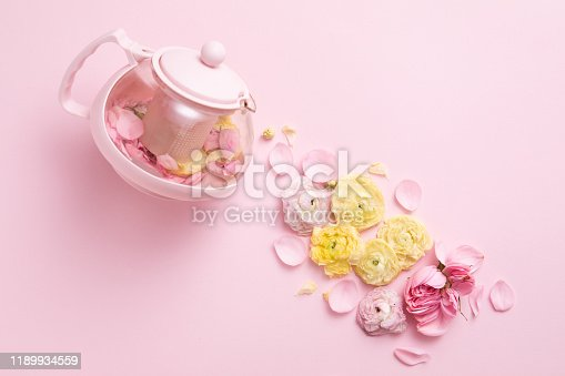 Top view of creative layout of pink teapot and tea cup with flowers on pink background.