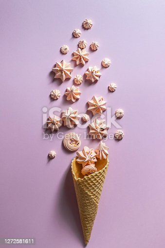 Top view of crispy ice cream waffle cone and marshmallows on pink background. Creative flat lay, copy space