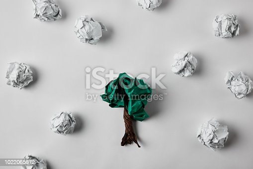 top view of crumpled papers in shape of tree on white surface