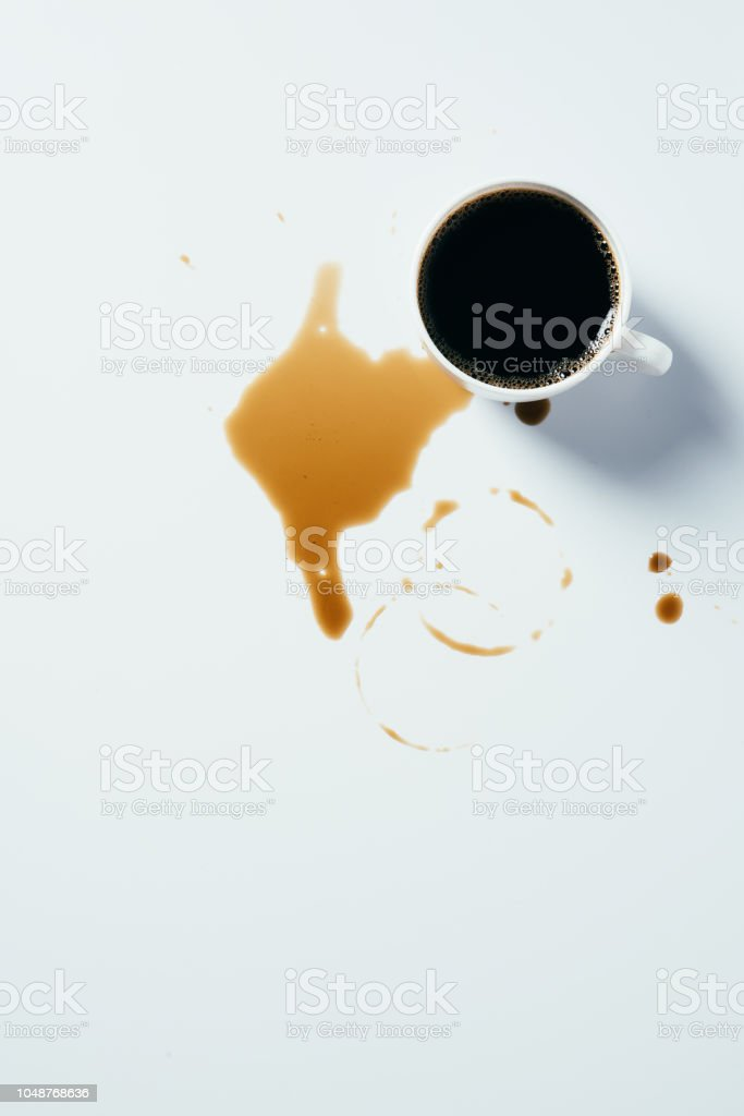 top view of cup of black coffee standing messy on white surface stock photo