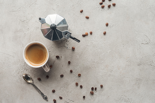 top view of cup of coffee and moka pot on concrete surface with spilled coffee beans