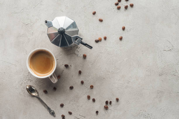 top view of cup of coffee and moka pot on concrete surface with spilled coffee beans top view of cup of coffee and moka pot on concrete surface with spilled coffee beans coffee pot stock pictures, royalty-free photos & images