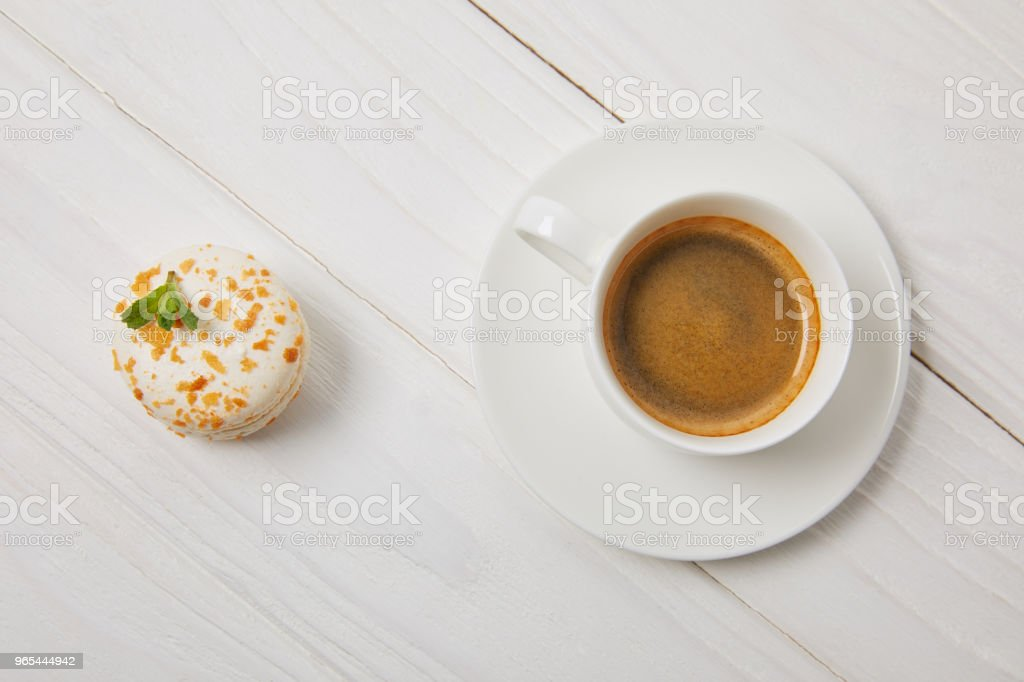 top view of cup of coffee with saucer and macaroon on white wooden table zbiór zdjęć royalty-free