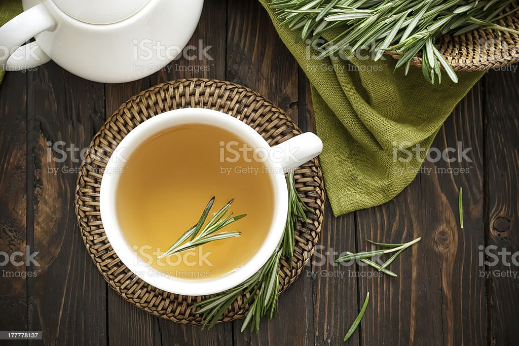 Top view of cup of rosemary tea on wooden table stock photo