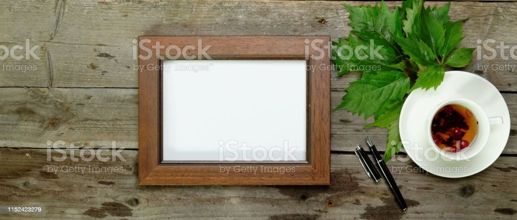 Flat lay on the old wood decorated with green leaves with white cup...