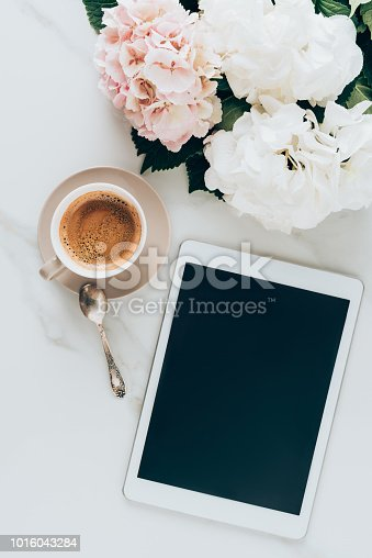top view of cup with espresso coffee, hortensia flowers and digital tablet with blank screen on marble surface