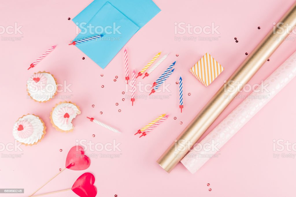Top view of cupcakes, colorful candles and wrapping paper on pink, birthday party concept 免版稅 stock photo