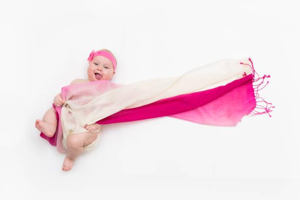 top-ansicht von niedlichen baby-mädchen in einem feenkostüm gekleidet, das ihren zungenflatternden langen schal und ihr stirnband herausragt. platz für text - wickelkleid lang stock-fotos und bilder