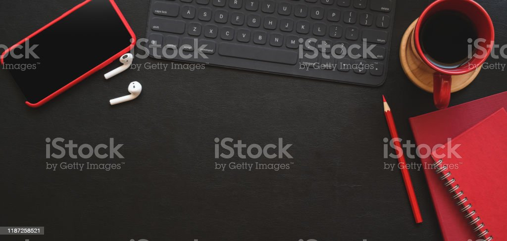 Top view of dark modern workplace with red office supplies and copy space on black table Top view of dark modern workplace with red office supplies and copy space on black table background Above Stock Photo