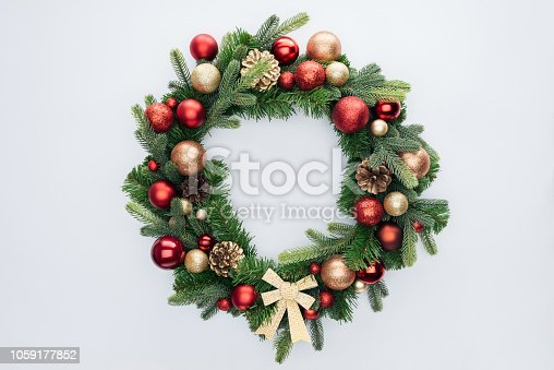 top view of decorative festive wreath with red and golden christmas toys isolated on white
