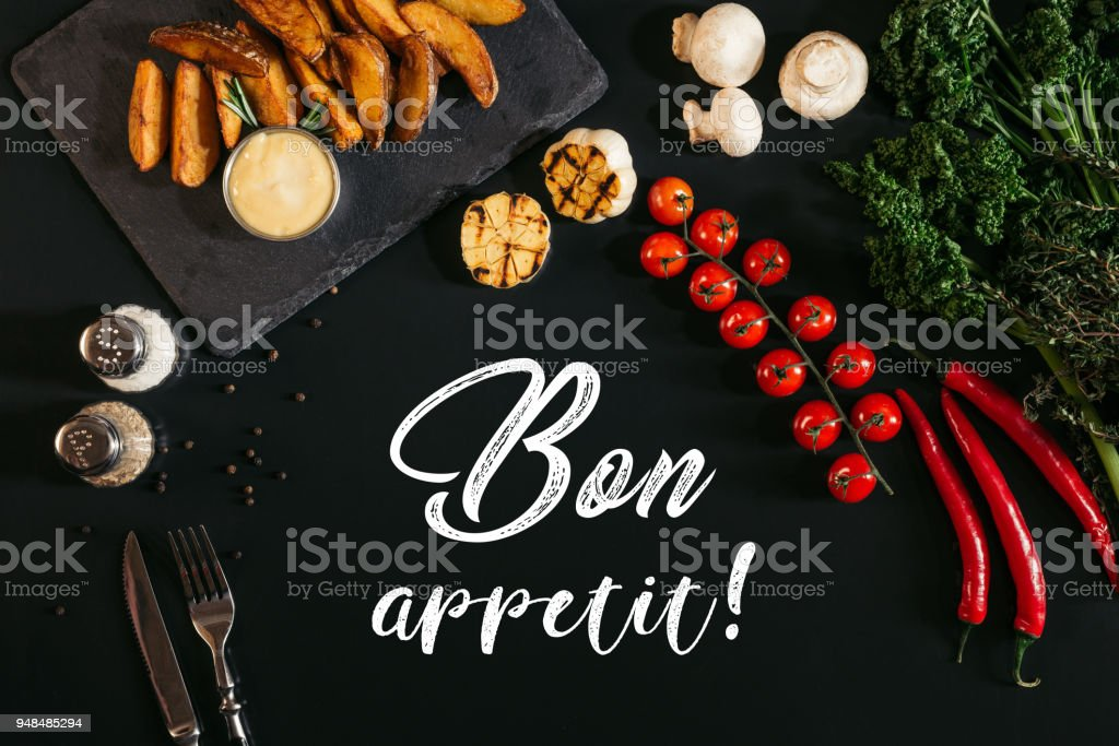 top view of delicious baked potatoes with sauce and spices, vegetables and inscription bon appetit on black stock photo