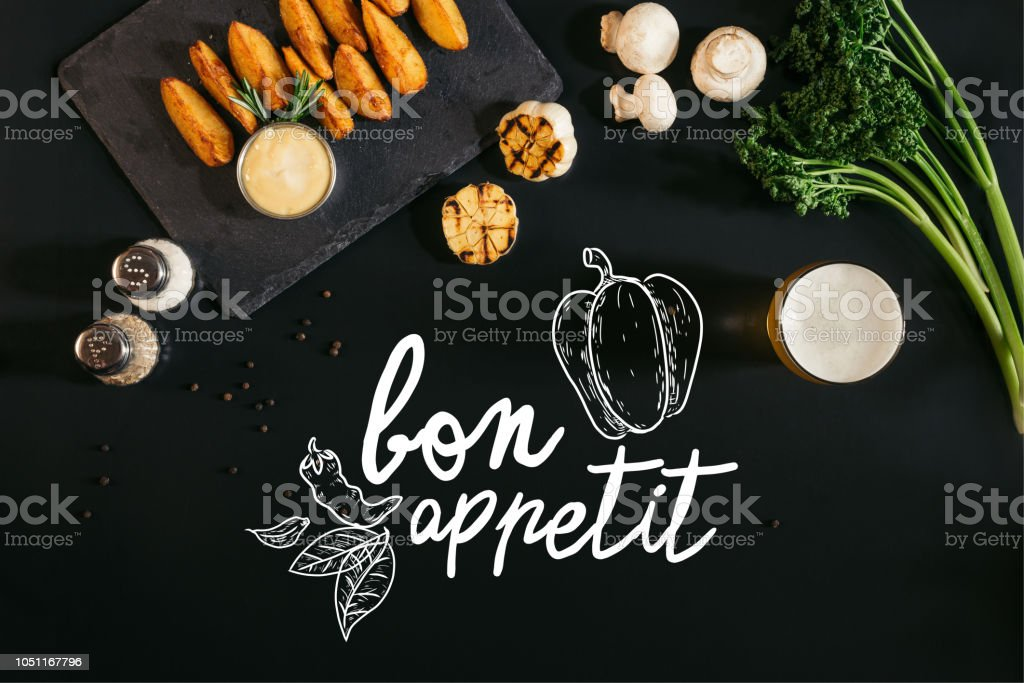 top view of delicious baked potatoes with sauce, spices and glass of beer on black with 'bon appetit' lettering stock photo