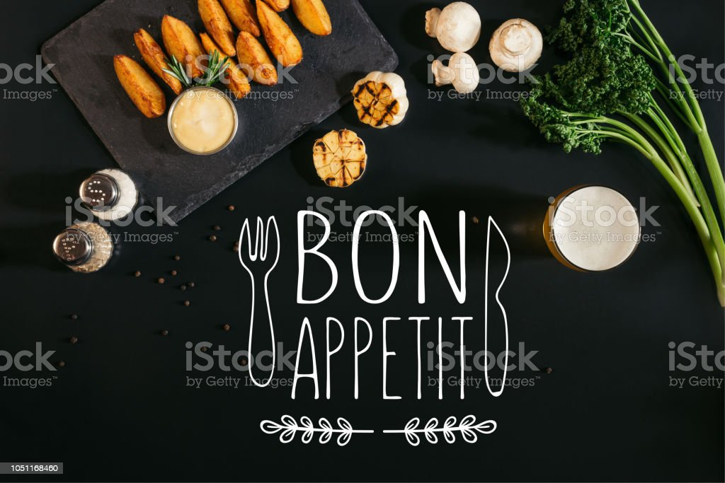 top view of delicious baked potatoes with sauce, spices and glass of beer on black with 'bon appetit' lettering with fork and knife stock photo