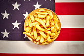 top view of delicious french fries on a plate on the background of the USA flag