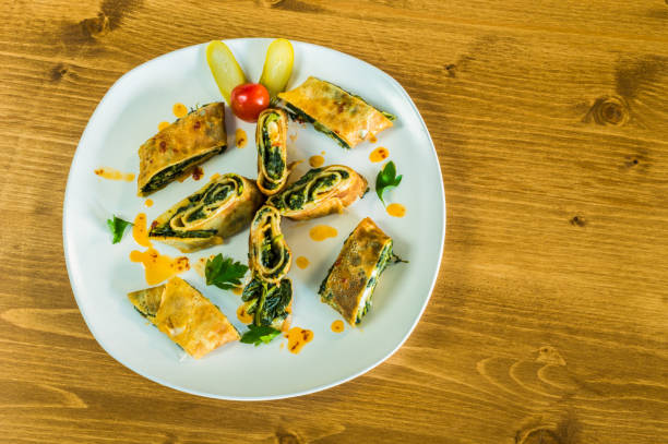 Top view of delicious wrapped crepe with spinach served on a white plate stock photo