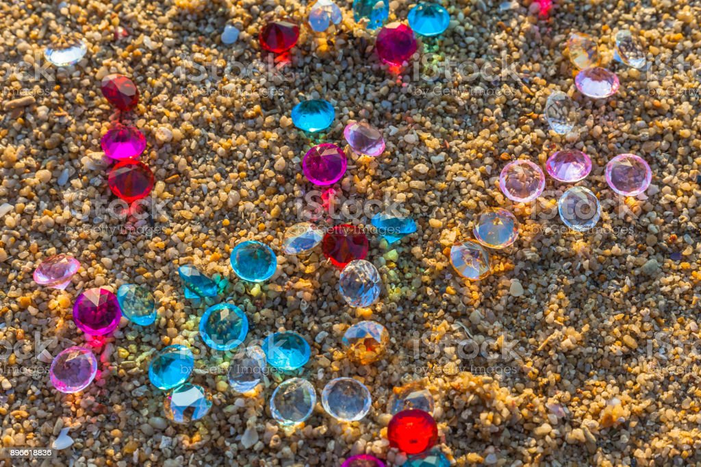 top view of diamonds scattered about on the beach. stock photo