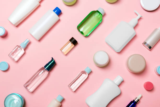 Top view of different cosmetic bottles and container for cosmetics on pink background. Flat lay composition with copy space stock photo