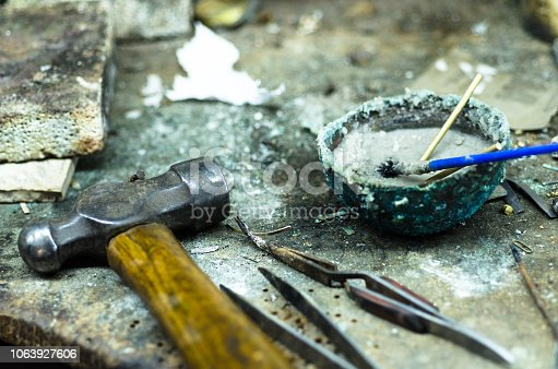 istock Top view of different goldsmiths tools on the jewelry workplace. Aerial view of tools over rustic wooden background. 1063927606