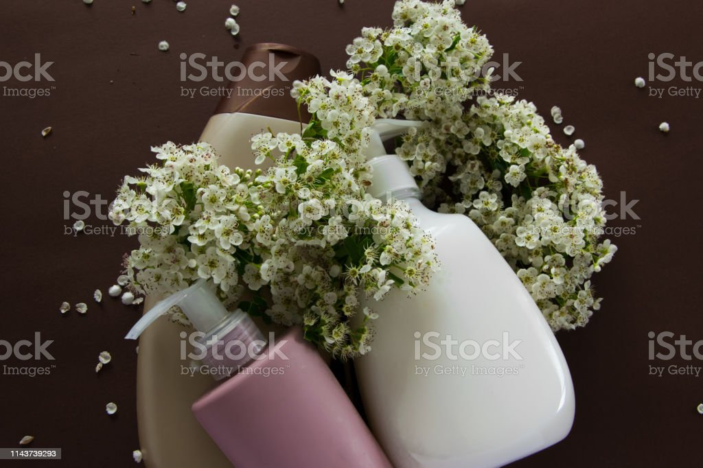 Top view of different hygienic products and flowers on brown...