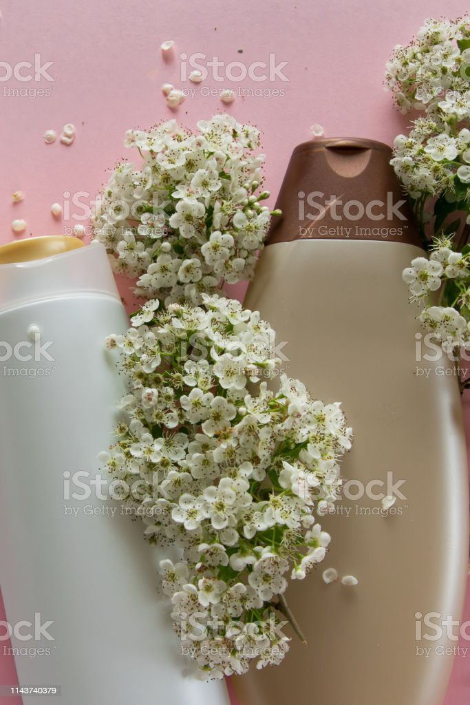 Top view of different hygienic products and flowers on fresh pink...