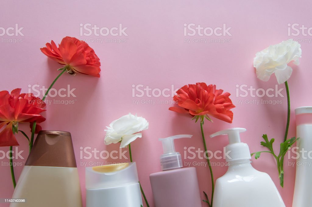 Top view of different hygienic/cosmetic products and flowers on fresh...