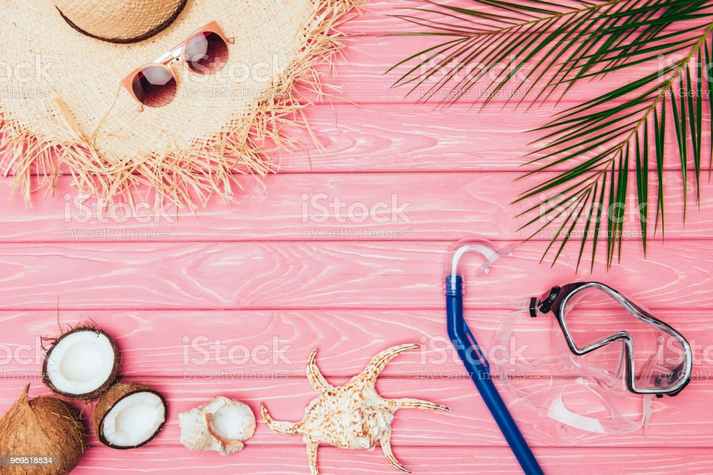 top view of different travel attributes on pink wooden surface stock photo