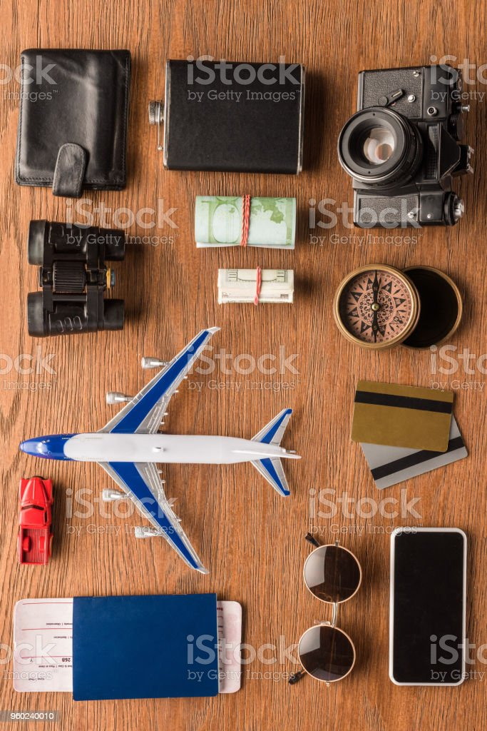 top view of different travel attributes on wooden surface stock photo