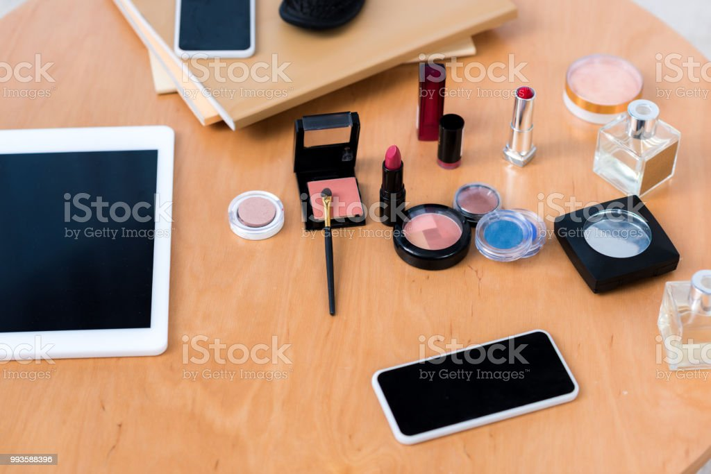 top view of digital devices and various cosmetics on table