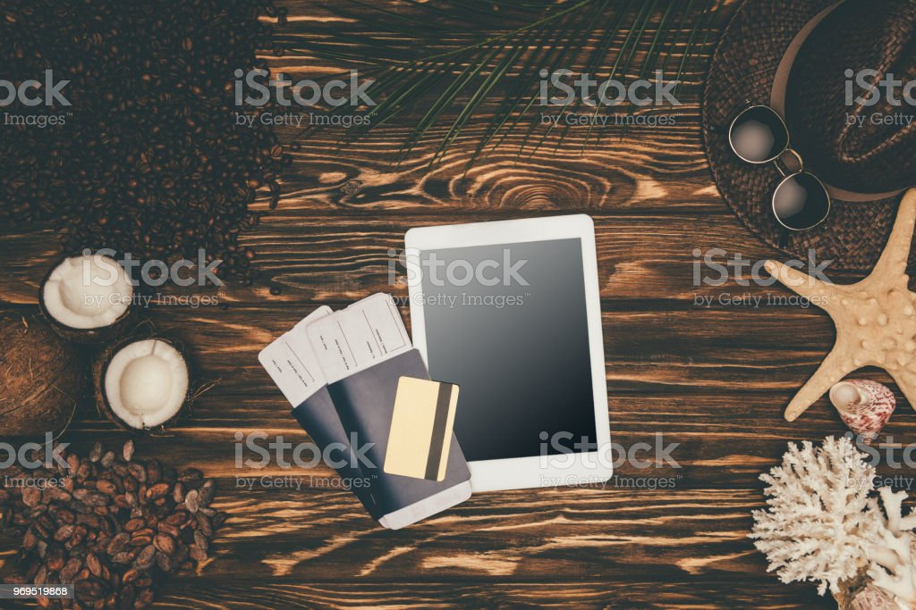 top view of digital tablet and flight tickets surrounded with various tropical travel attributes on wooden surface stock photo