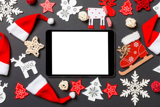 Top view of digital tablet. New Year decorations on black background. Merry Christmas concept stock photo