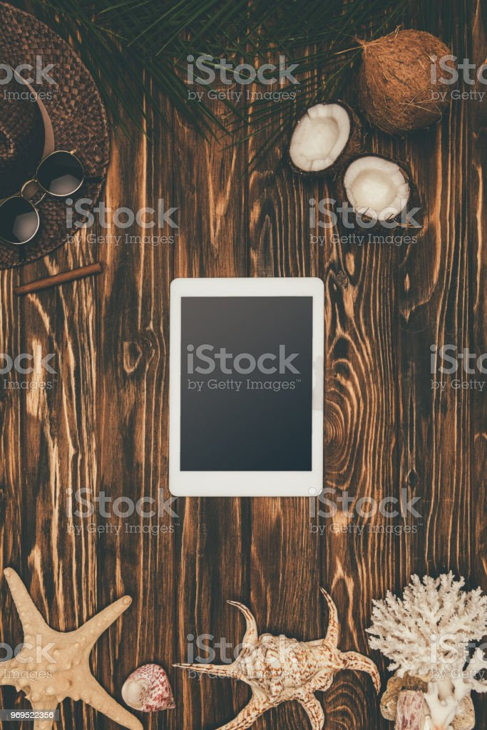 top view of digital tablet on wooden surface surrounded with various tropical travel attributes stock photo
