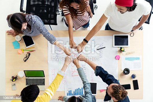 istock Top view of diverse people of creative team group join hands circle together in collaboration concept with smartphone, mobile phone, tablet and computer laptop on table. Young asian start up meeting. 1060957404