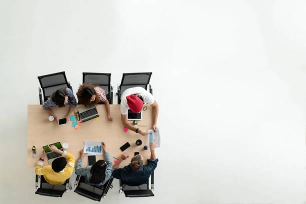 vista superior de diversas personas de equipo creativo utilizando smartphone, teléfono móvil, tableta y ordenador portátil. vista aérea de creativos jóvenes asiáticos comenzar reunión. con espacio de copia de texto de relleno. - reunión evento social fotografías e imágenes de stock