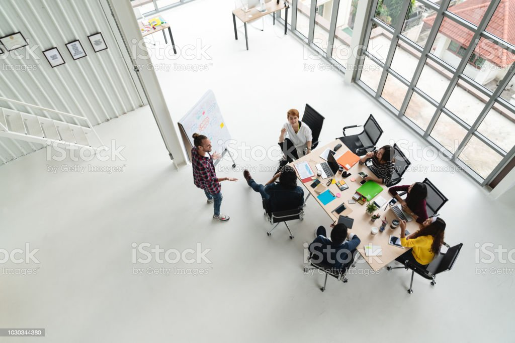 Top view of diverse people of creative team group using smartphone, mobile phone, tablet and computer laptop while meeting. Overhead view of asian young creative start up meeting with wide angle view. royalty-free stock photo