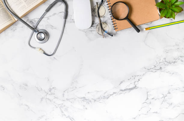 Top view of doctor desk marble table with stethoscope Top view of doctor desk marble table with stethoscope and notebook, other supplies with copy space for input the text. flat lay. reference book stock pictures, royalty-free photos & images