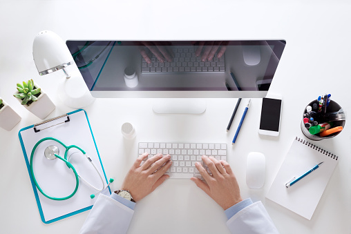 istock Top view of doctor sitting at the desk and using computer 670822500