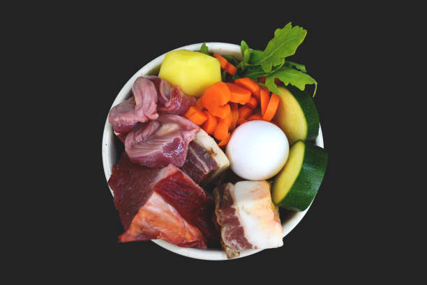 top view of dog filled with mixture of biologically appropriate raw food containing meat chunks, vegetables, egg on dark black background - desperdício alimentar imagens e fotografias de stock