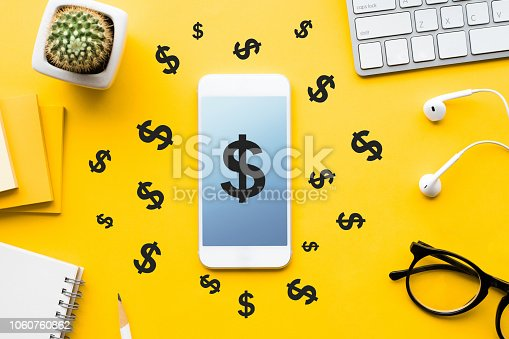 1060760900istockphoto Top view of dollar icon on mock up smartphone and modern accessories,supplies on table background.business financial,online banking,making money concepts 1060760862