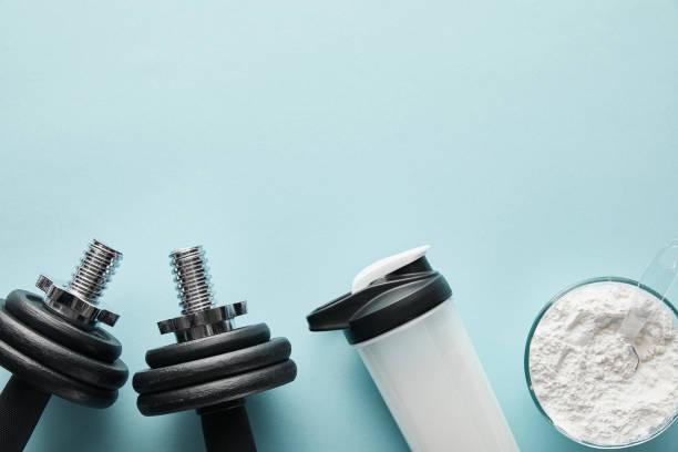 スポーツボトルと青のタンパク質パウダーの近くのダンベルのトップビュー - プロテイン ストックフォトと画像