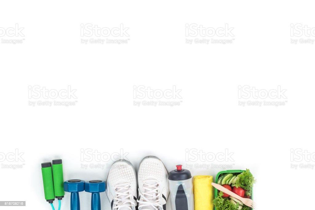 vista superior de pesas, saltar la cuerda, zapatos de los deportes, botella de agua y verdura ensalada aislado en blanco foto de stock libre de derechos