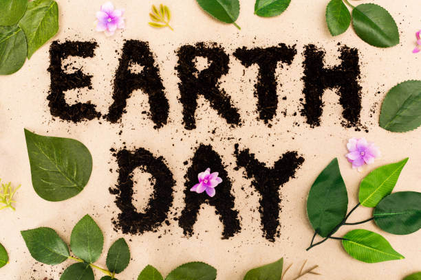 top view of earth day lettering with leaves and buds on beige background - earth day stock pictures, royalty-free photos & images