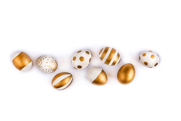 draufsicht der ostereier gefärbt mit goldener farbe in verschiedenen mustern. gestreifte und gepunktete bauformen. weißen hintergrund. kopieren sie raum. - besondere geschenke stock-fotos und bilder