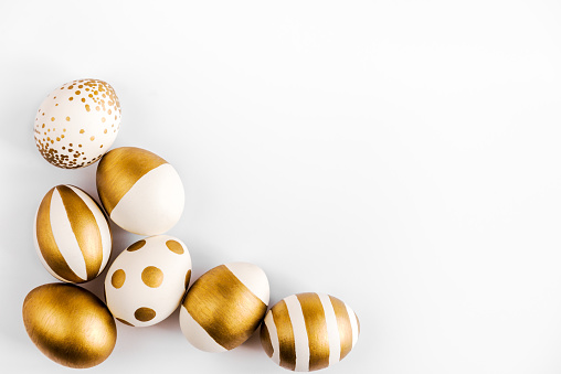 Top view of easter eggs colored with golden paint. Various striped and dotted designs. White background.