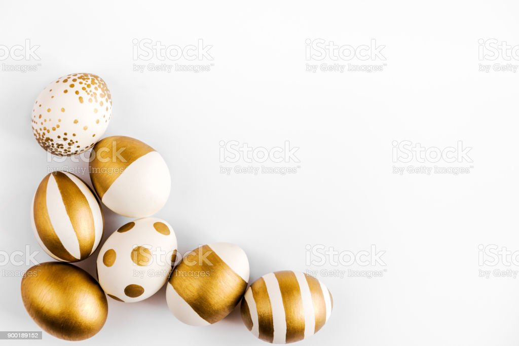 Top view of easter eggs colored with golden paint. Various striped and dotted designs. White background. stock photo