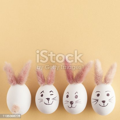 Top view of Easter eggs making with pink bunny ears in different patterns. Pastel yellow background. Copy space.