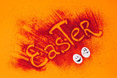 istock top view of easter sign made of red sand with chicken eggs with smileys on orange 928901830