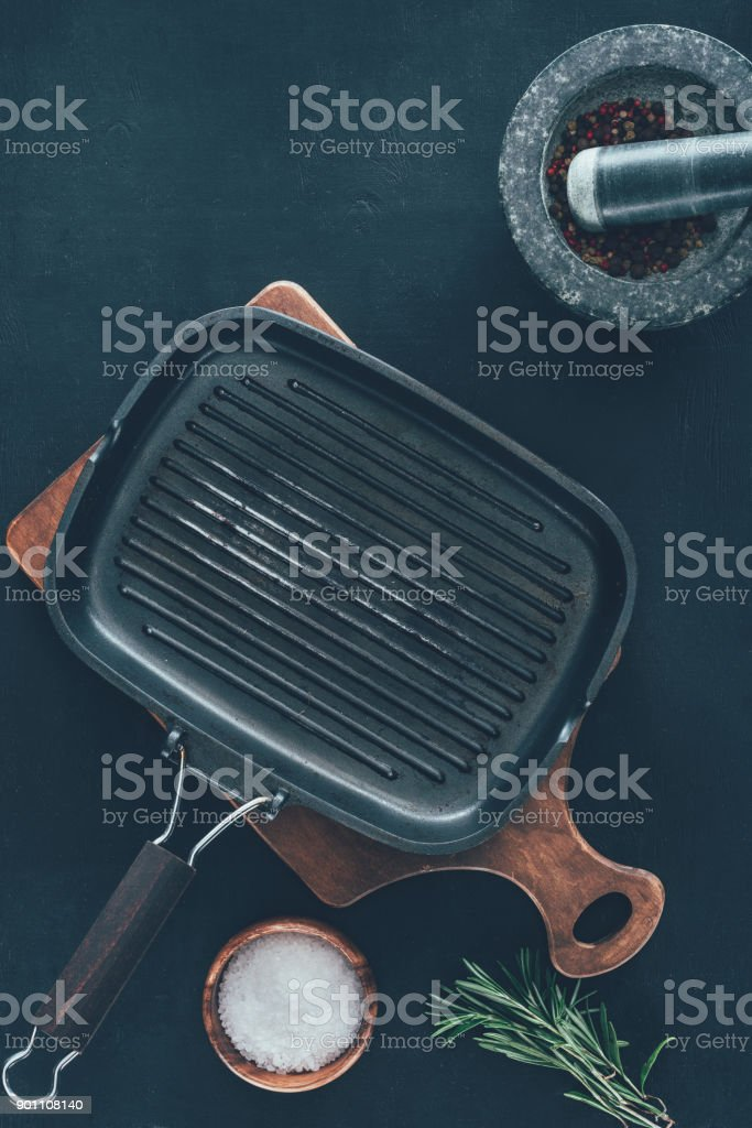 top view of empty grill pan with spices on black tabletop stock photo