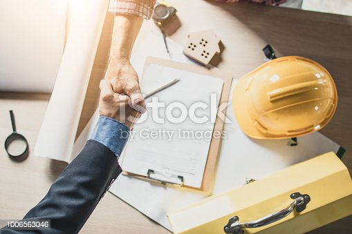 912867216istockphoto Top view of engineer and businessman shake hands on working table at working site 1006563046